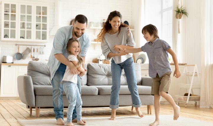 A family of four with a mother, a father, a younger daughter and an oldest brother standing and playing with each other in their living room by their sofa.