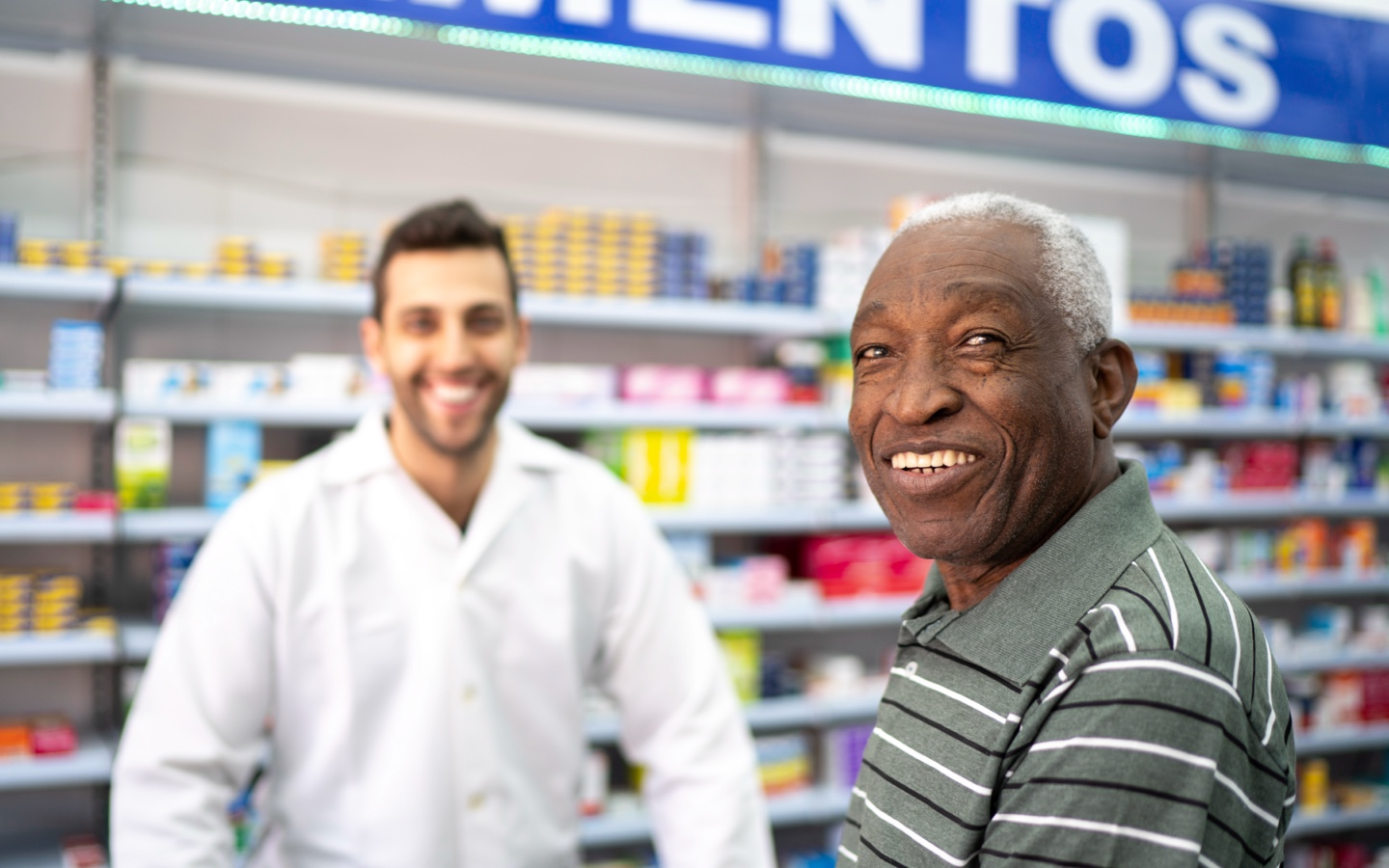 Old man at a pharmacy counter with a pharmacy attendant both smilling to the camera.