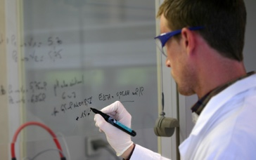A male scientist in its thirties writing a formula on a transparent board with a black pen.