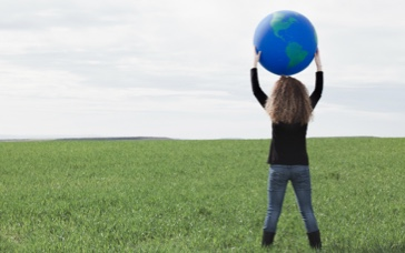 Young girl with long blond curly hair standing up and holding a globe baloon in a field background.