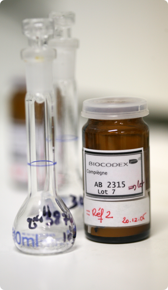 Glass beaker with Biocodex capsule bottle
